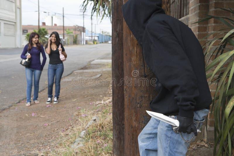 Rånarenederlag bak träd och vänta på två flickor arkivfoto