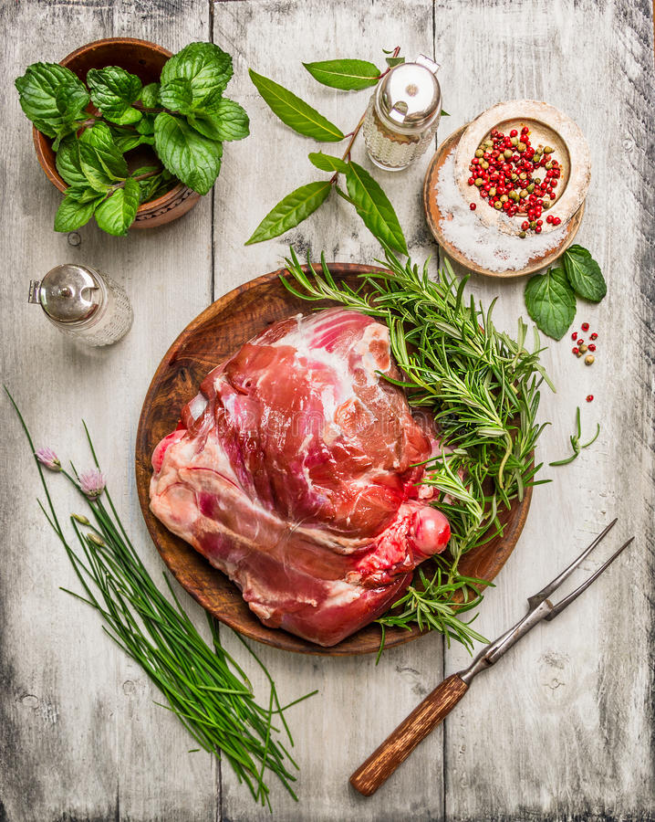 Rått ben av lammet med köttgaffeln och nya örter för att laga mat på vit träbakgrund arkivbild