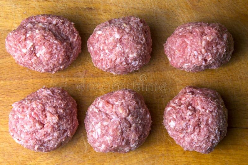 Rått finhacka små pastejer i laga mat kotletter förbereds för skärbräda royaltyfri bild