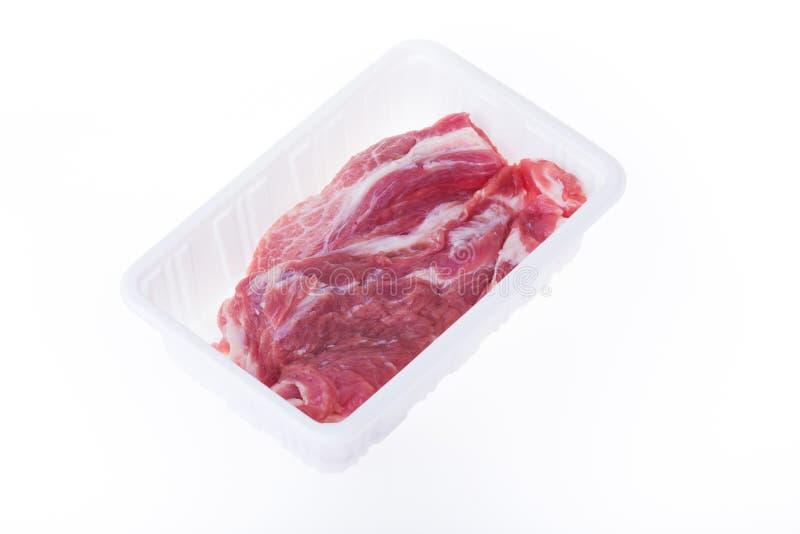 Rått griskött i packe för plast- ask arkivfoto