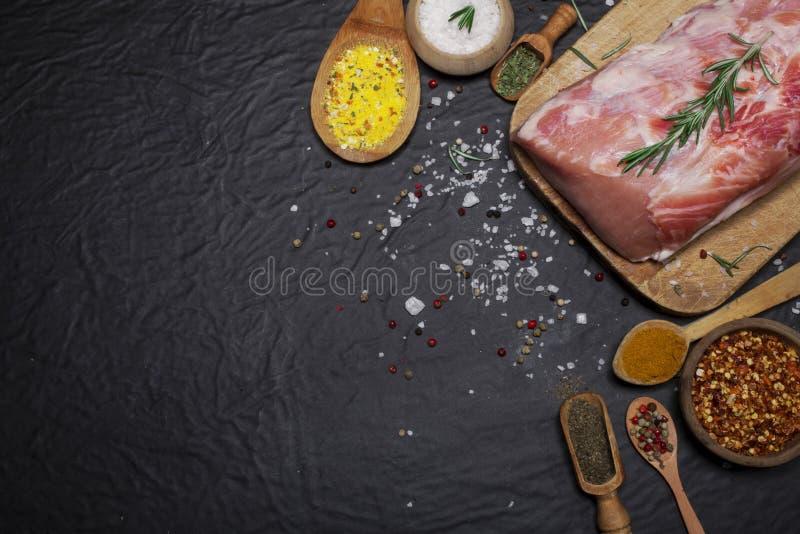 Rått grisköttkött på en skärbräda med rosmarin och kryddor arkivbilder