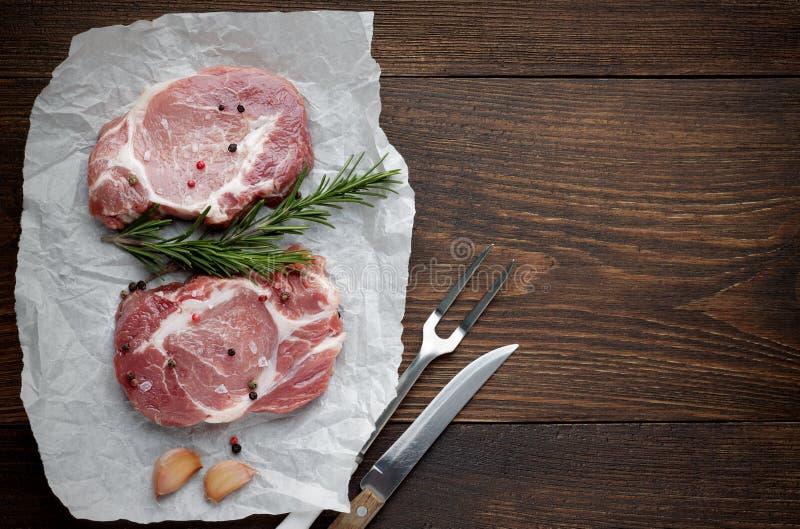 Rått grisköttkött på vitt pergament med rosmarin, vitlök och kryddor på trätabellen royaltyfria bilder