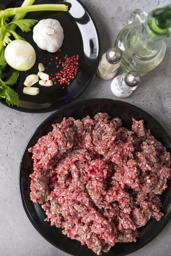 Rått jordnötkött på en svart platta, lökar, vitlök, selleri, peppar på en platta, saltar shaker, en flaska av olja royaltyfri foto