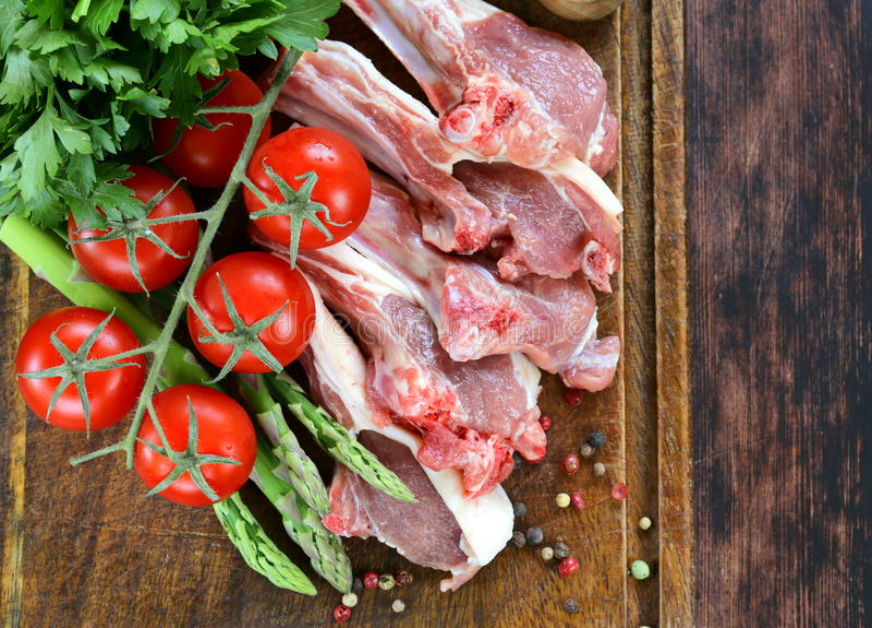 Rått kött, lammkotletter med grönsaker arkivfoto