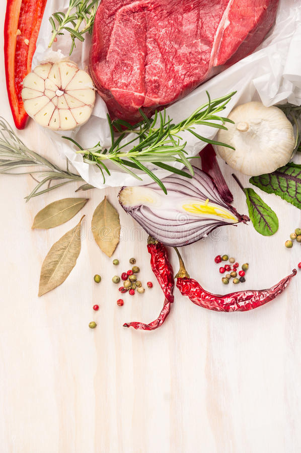 Rått kött med örter och kryddor: lagerblad vitlök, peppar på vit träbakgrund, bästa sikt, slut upp royaltyfri fotografi