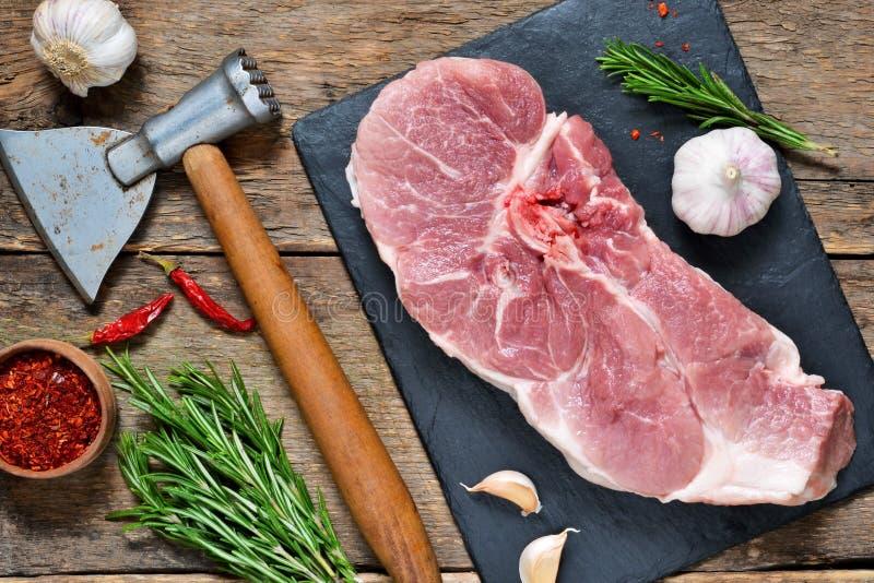 Rått kött med kryddor och en yxa på en träbakgrund royaltyfria bilder