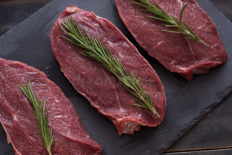 Rått kött, nötköttbiff med rosmarin på svart bakgrund Tre objekt close upp royaltyfri foto