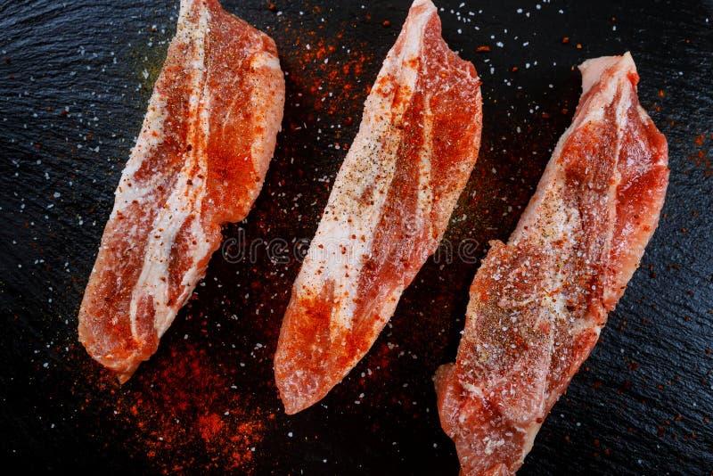 Rått kött på mörk bakgrund Rå grisköttbiff med örter, olja och kryddor Pork med grönsaker på träbräde royaltyfri fotografi
