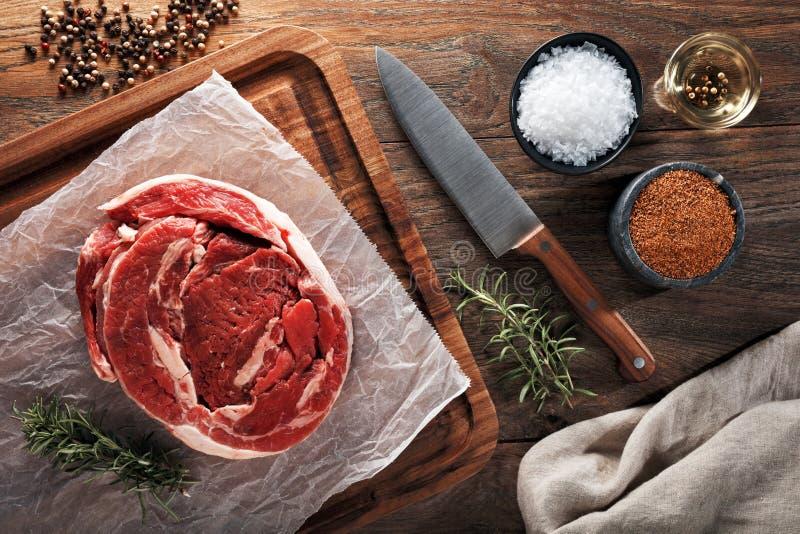 Rått kalvbringakött på vitt laga mat papper och den träbitande tabellen Dercorated med örter, kryddor och kockkniven royaltyfria foton