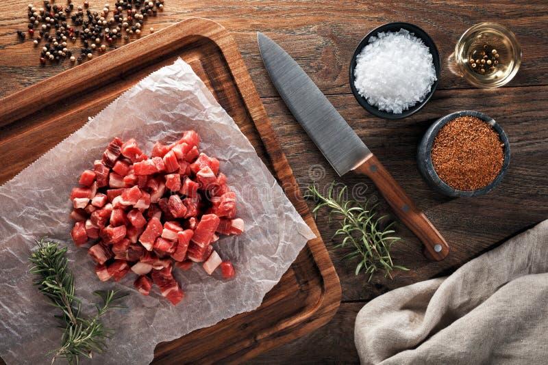 Rått kalvkött som huggas av in i små stycken på vitt laga mat papper och den träbitande tabellen royaltyfri bild