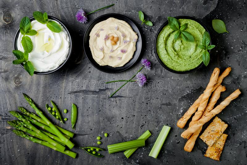 Rått mellanmålbräde för gröna grönsaker med olika dopp Yoghurtsås eller labneh, hummus, örthummus eller pesto med smällare, griss royaltyfri foto