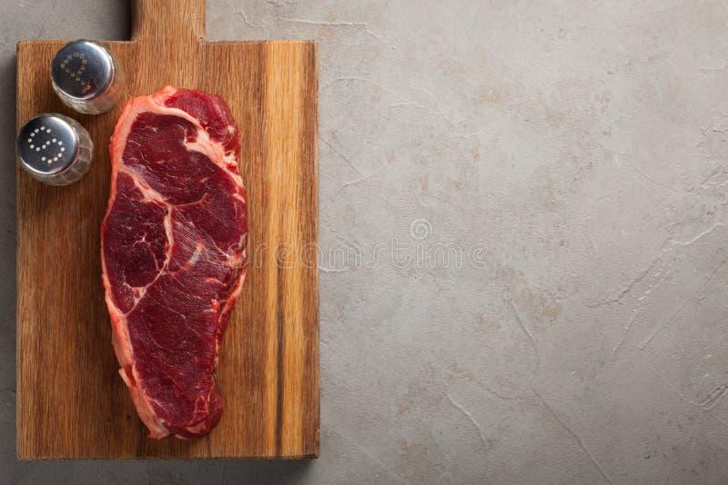 Rått nötkött marmorerade biff med vitt bestick för tappning på gammal stenbakgrund Ett stycke av kött med peppar och saltar på et arkivbilder
