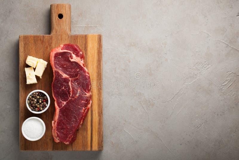Rått nötkött marmorerade biff med vitt bestick för tappning på gammal stenbakgrund Ett stycke av kött med peppar och saltar på et royaltyfri fotografi