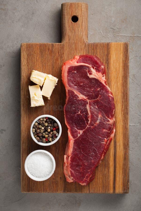 Rått nötkött marmorerade biff med vitt bestick för tappning på gammal stenbakgrund Ett stycke av kött på ett träbräde Biff New Yo arkivfoto