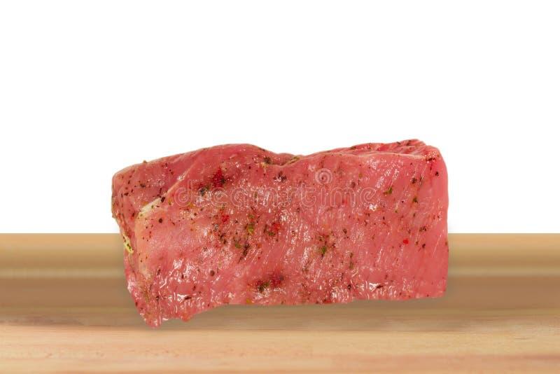 Rått nötkött på träskärbrädan royaltyfri fotografi