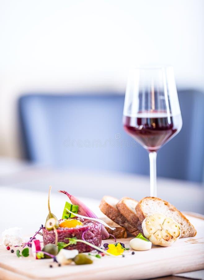 rått nötkött Smaklig tartarbiffstek Klassisk tartarbiffstek på träbräde Ingredienser: Chili för vitlök för ägg för peppar för råt arkivfoton