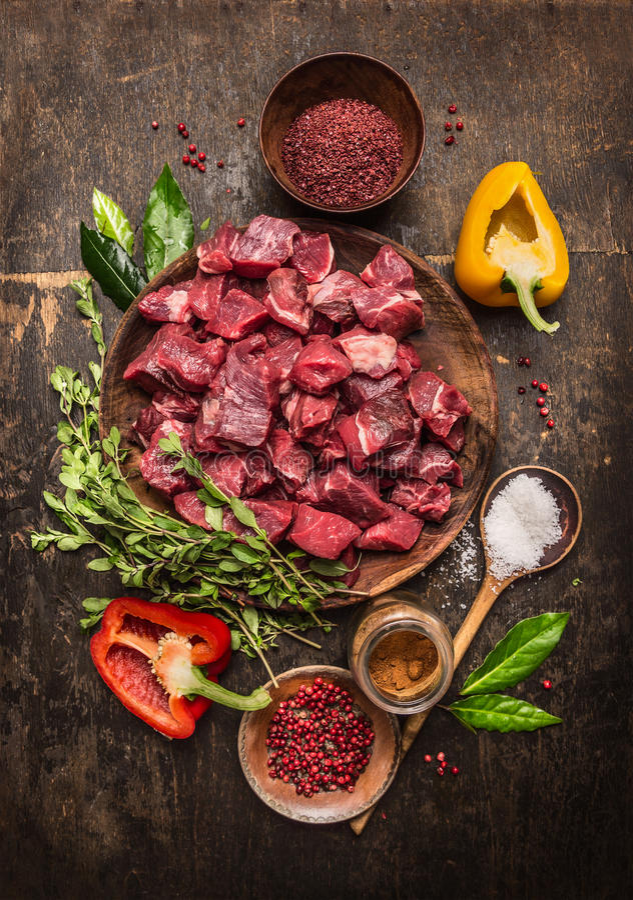Rått okokt kött som skivas i kuber med nya örter, grönsaker och kryddor på lantlig träbakgrund, ingredienser för kalops arkivfoton