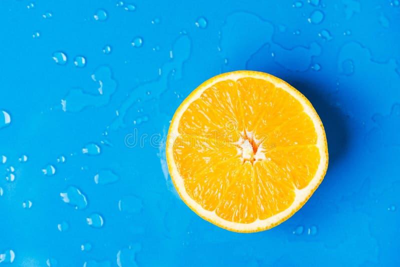 Rått saftigt citrusfruktsnitt i halv apelsin på våt blå bakgrund med vattendroppfärgstänk Drinkar för sommardryckuppfriskningar royaltyfri foto
