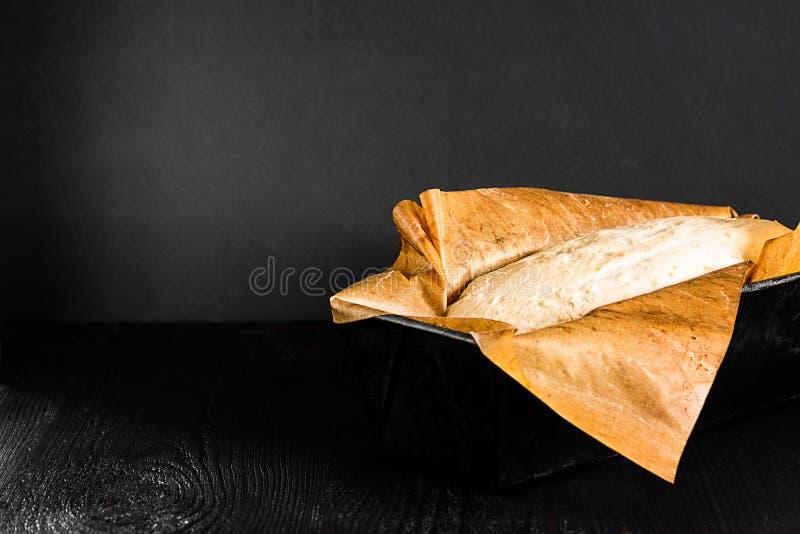 Rått surt degbröd släntrar, i att baka metallfyrkantformen med bakelsepergament på mörk svart träbakgrund Stekhett bröd recept arkivfoton