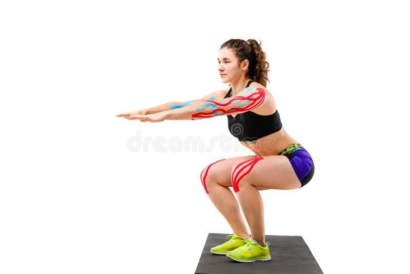 Réadaptation de bande de cinésiologie de thème et santé des athlètes Belle fille faisant un exercice accroupi sur une couverture  photographie stock