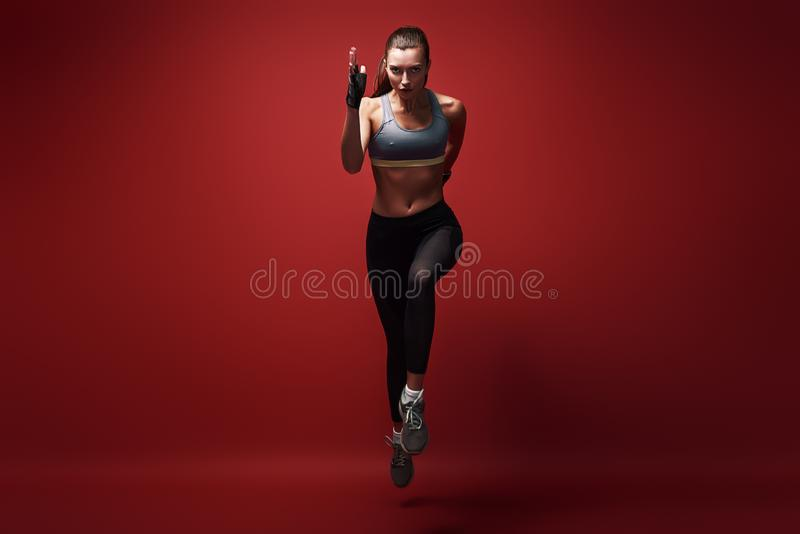 Réalisation des meilleurs résultats Jeune sportive sprintant vers la caméra au-dessus du fond rouge photo stock