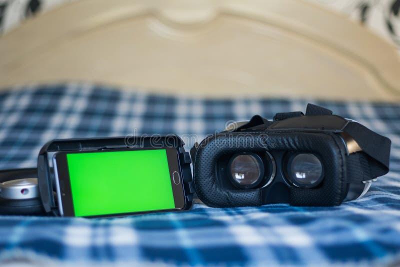 Réalité virtuelle, helmetбsmartphone de VR et écouteurs avec le vert images stock
