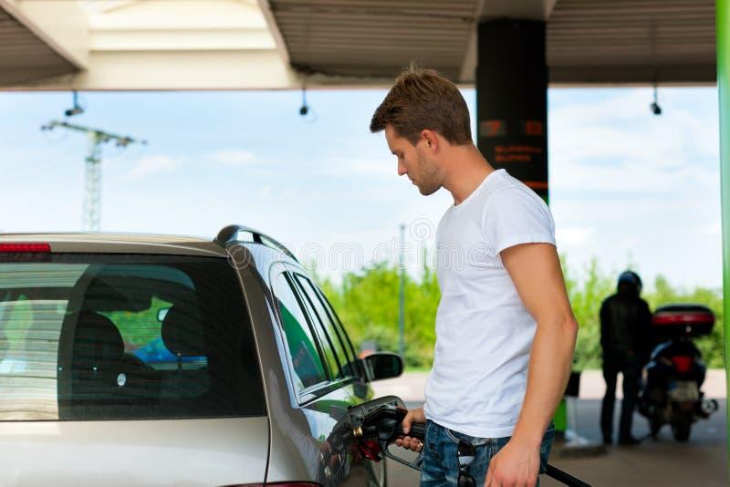 Réapprovisionnez en combustible le véhicule sur une station service images libres de droits