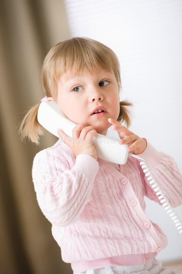 Récepteur téléphonique de fixation de petite fille appelle photo libre de droits