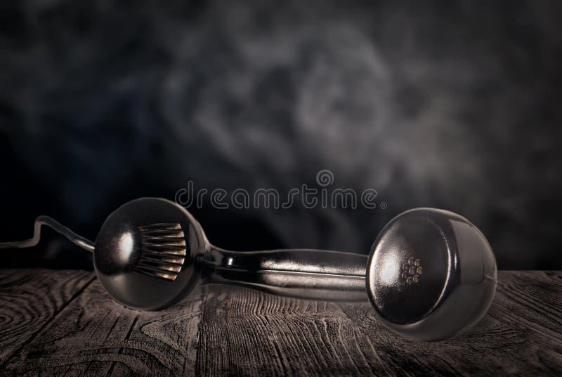 Récepteur téléphonique noir sur une table en bois images libres de droits
