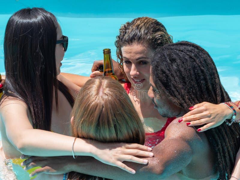 Réception au bord de la piscine avec de la bière Personnes multiraciales, garçon noir et filles caucasiennes, chinoises et russes image libre de droits