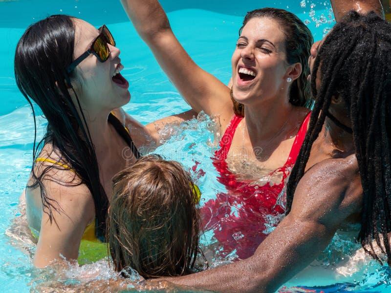 Réception au bord de la piscine avec de la bière Personnes multiraciales, garçon noir et filles caucasiennes, chinoises et russes images stock