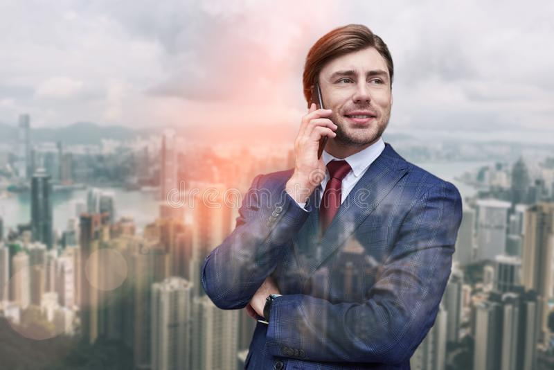 Réception de bonnes nouvelles Jeune homme d'affaires gai parlant par le téléphone et souriant tout en se tenant contre du paysage image stock