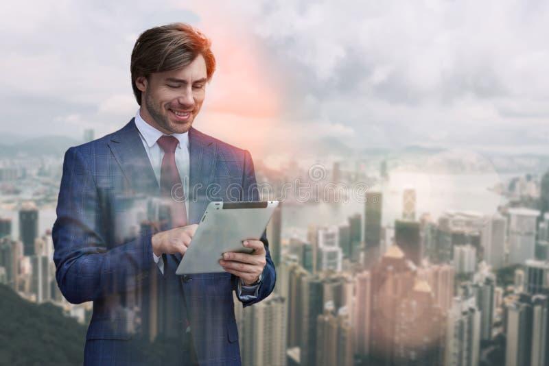 Réception de bons examens Homme d'affaires positif travaillant au comprimé numérique tout en se tenant contre des immeubles de bu photographie stock libre de droits