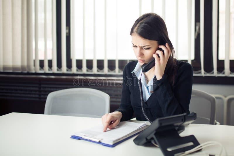 Réception de l'appel téléphonique de mauvaise nouvelle Regard confus vérifiant des notes et des écritures Directeur résolvant l'e photo stock