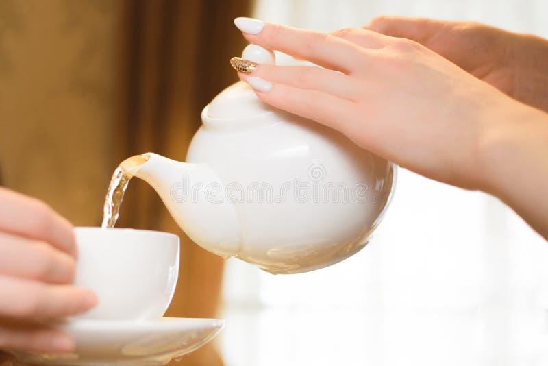 Réception de thé Les femmes versent le thé vert dans une tasse blanche photos stock