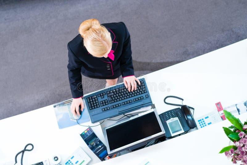 Réceptionniste d'hôtel travaillant à la salle des marchés photographie stock libre de droits