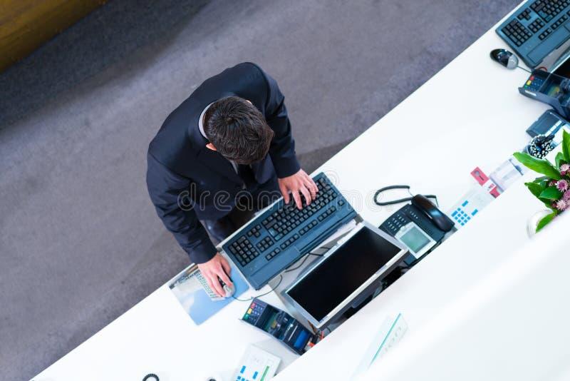 Réceptionniste d'hôtel travaillant à la salle des marchés photos libres de droits