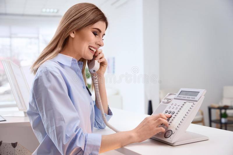 Réceptionniste féminin parlant au téléphone au contrôle d'hôtel photographie stock libre de droits