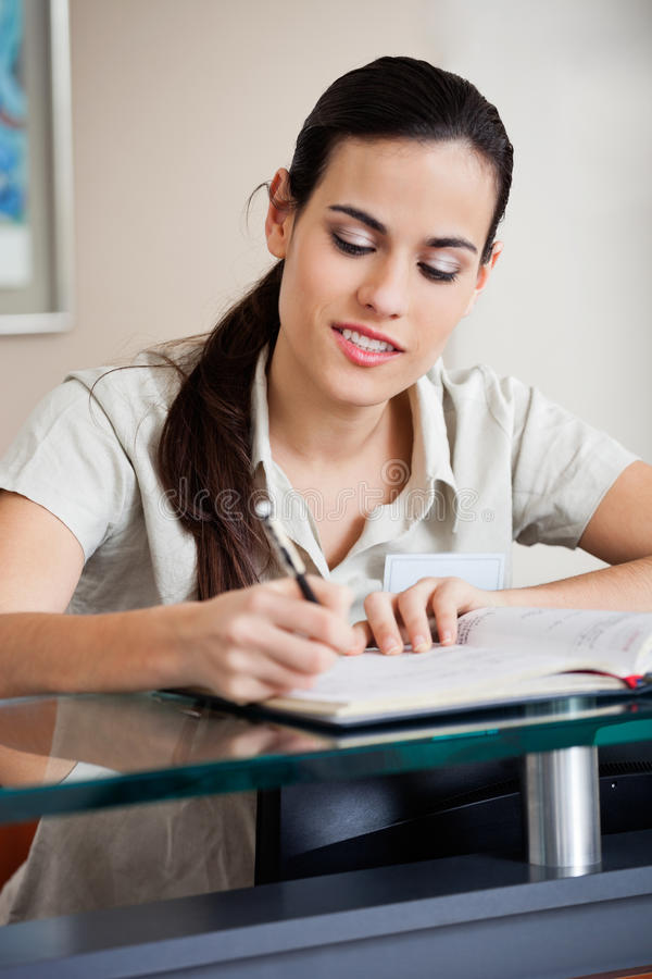 Réceptionniste féminin Writing In Book image stock