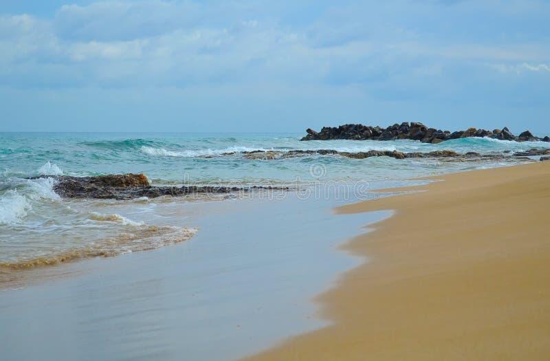 Récif rocheux sur une plage sablonneuse avant la tempête images libres de droits