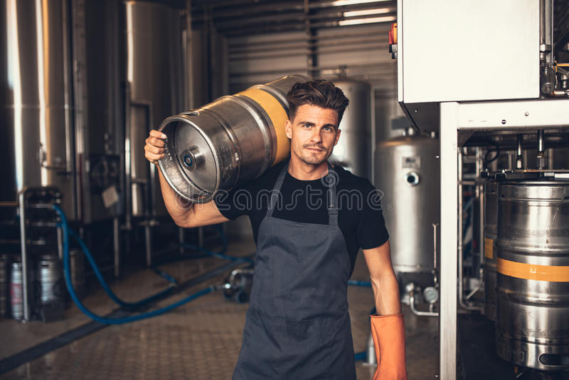 Récipient de transport en métal de brasseur masculin à l'usine de brasserie images libres de droits
