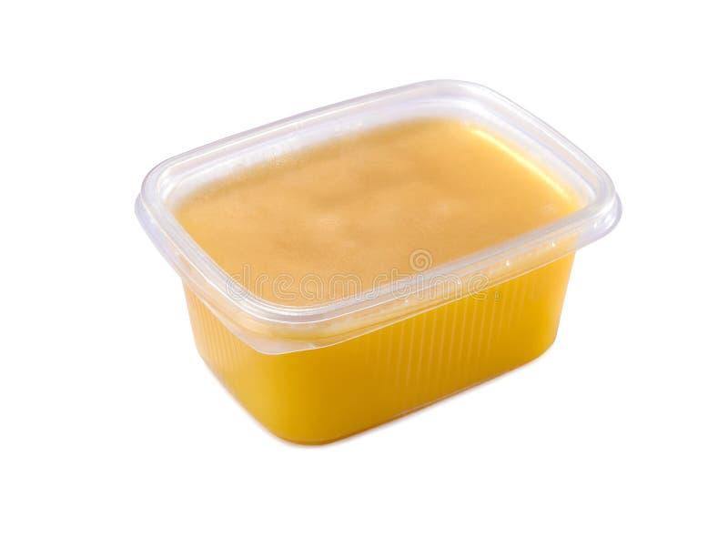 Récipient en plastique avec du beurre de ghee d'isolement sur le blanc photo stock