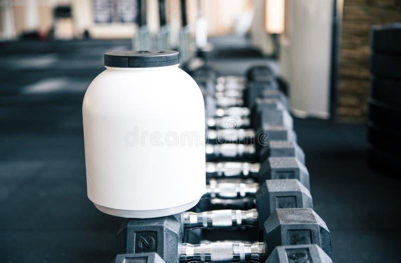 Récipient en plastique avec la nutrition de sports sur des haltères photo stock