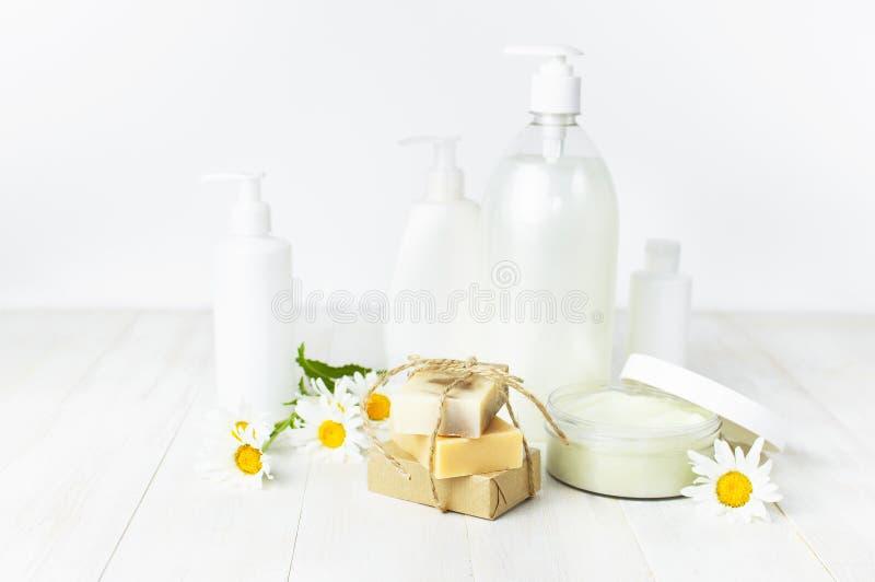 Récipient en plastique ouvert avec de la crème, les savons faits main, les conteneurs cosmétiques blancs de bouteille et la fleur image libre de droits