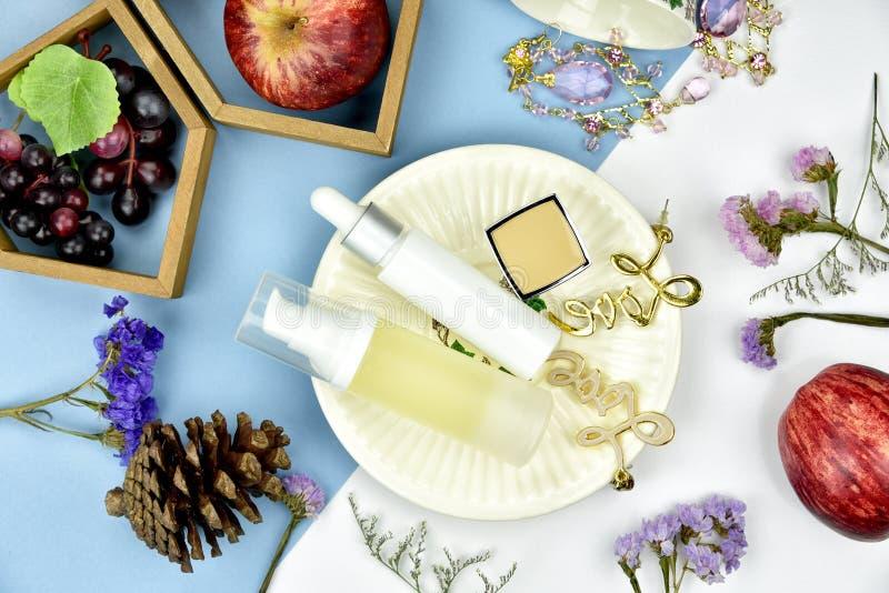 Récipients cosmétiques de bouteille avec des ingrédients d'essence de vitamine de fruit, maquette de marquage à chaud images stock