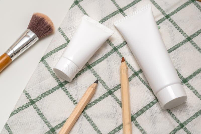 Récipients cosmétiques de bouteille avec les feuilles de fines herbes vertes, label vide photo stock
