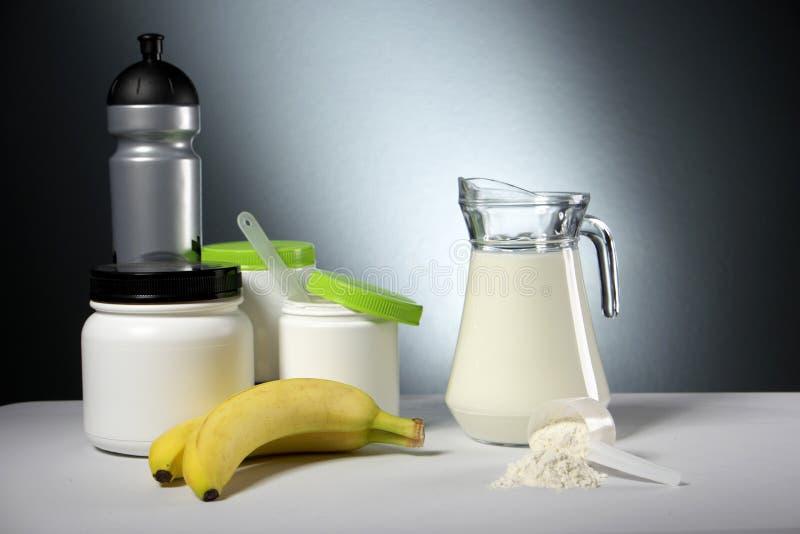 Récipients de supplément de nutrition de sport avec la cruche de lait photos stock