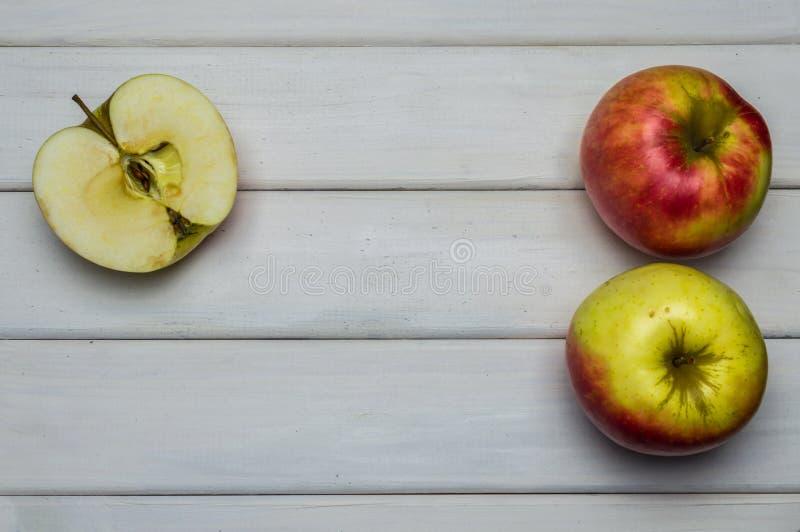 Récolte mûre rouge et verte de totalité et de coupe de pommes d'automne, de ci-dessus sur la table en bois blanche photographie stock libre de droits