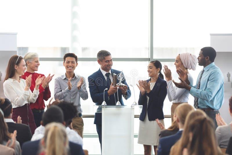 Récompense de participation d'homme d'affaires au podium avec des collègues dans un séminaire d'affaires photos libres de droits