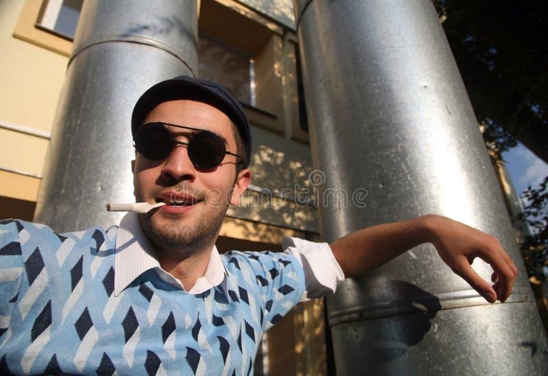 Récréation de jeune homme et cigarette de fumée